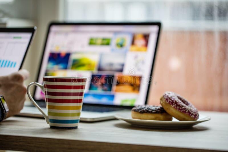 Equipaggi lavorare al taccuino, con una tazza di caffè fresca immagini stock
