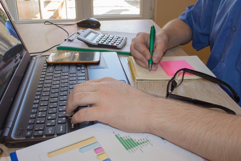 Equipaggi lavorare alla scrivania con il calcolatore, un computer, una penna ed il documento Uomo che conta soldi e che effettua  fotografie stock libere da diritti