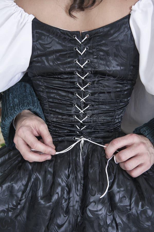 Equipaggi le mani che sciolgono il corsetto della donna in vestito medievale fotografia stock libera da diritti