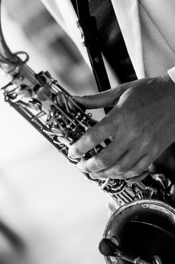 Equipaggi le mani del ` s con il sassofono sul fondo di Borgogna Fotographia in bianco e nero fotografia stock libera da diritti