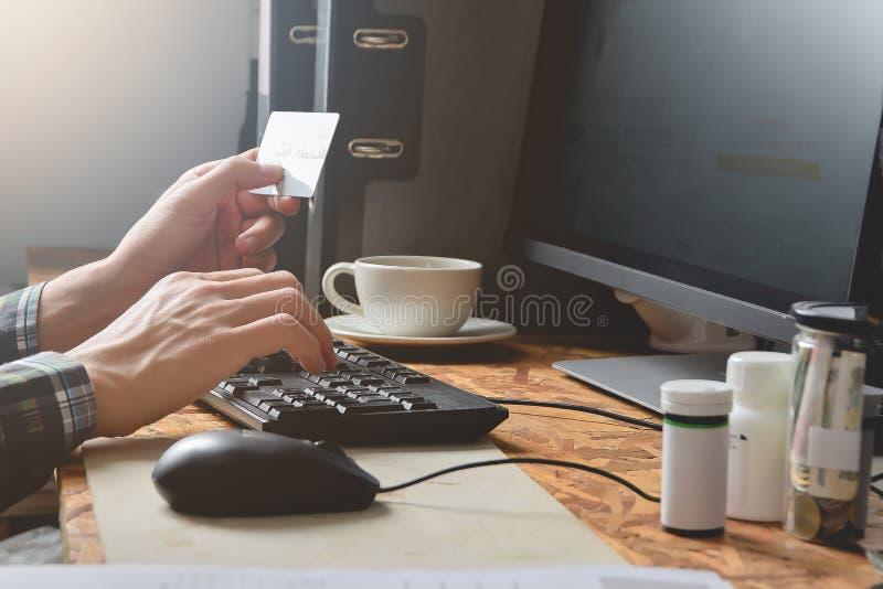 Equipaggi le mani facendo uso del pc del computer per la carta di credito online della tenuta e di acquisto per il negozio di pag fotografie stock