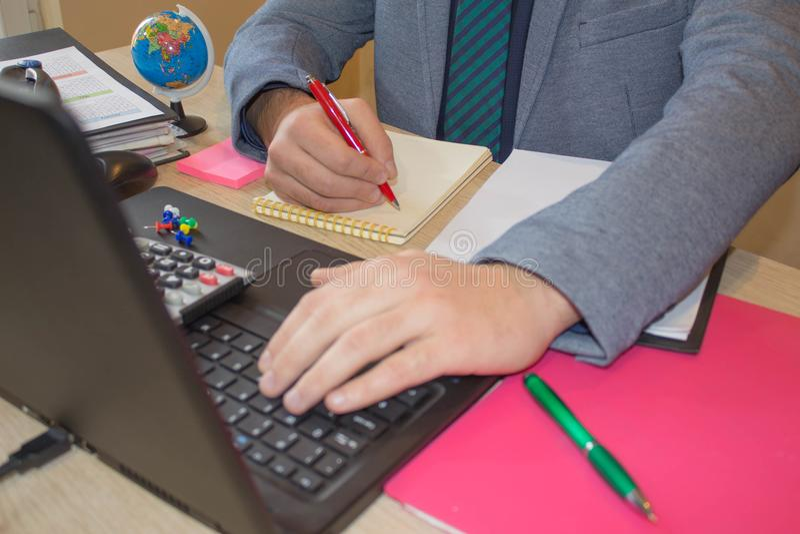 equipaggi le note di scrittura dal computer sulla tavola di legno Equipaggi la mano con la penna, il calcolatore ed il computer s immagini stock libere da diritti