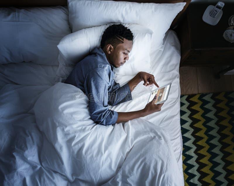 Equipaggi a letto facendo uso di un dispositivo digitale nello scuro fotografie stock