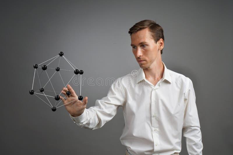 Equipaggi lo scienziato che lavora con il modello della molecola o del reticolo cristallino fotografia stock