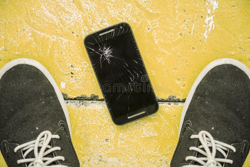 Equipaggi lo sguardo giù fra le sue scarpe sul pavimento del telefono cellulare graffiato e tagliato il suo dello schermo dopo es fotografie stock libere da diritti