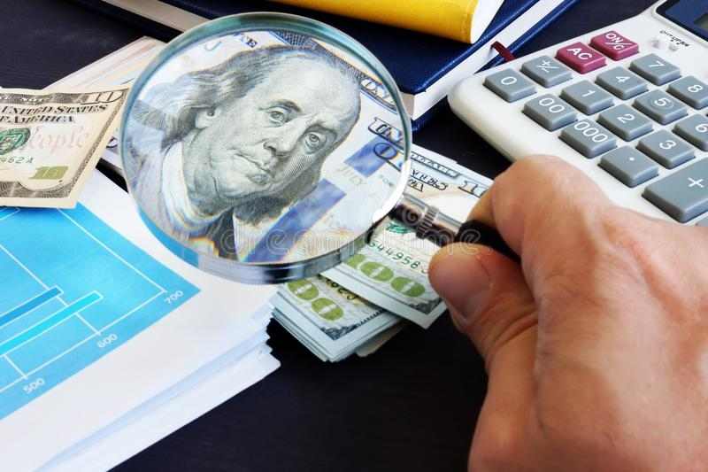 Equipaggi lo sguardo tramite la lente d'ingrandimento su una banconota del dollaro Verifica e ricerca finanziaria fotografia stock libera da diritti