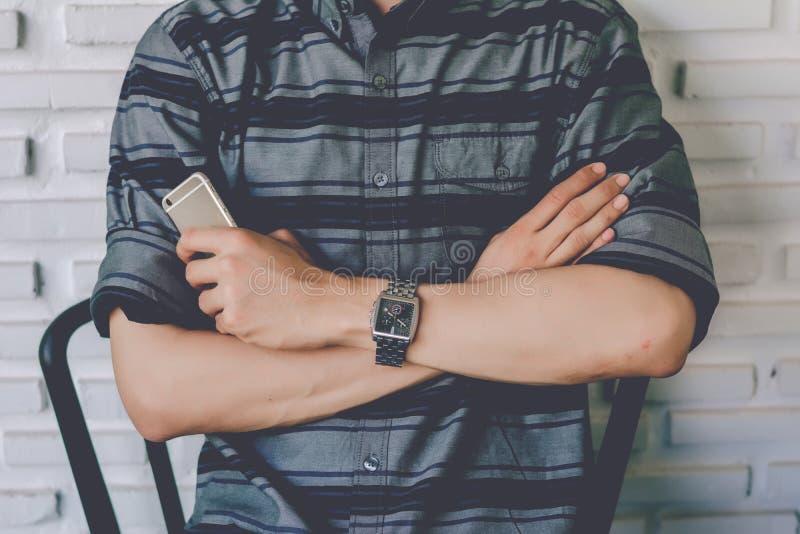 Equipaggi lo smartphone della tenuta ed attraversi un braccio del ` s isolato sul fondo della parete immagini stock
