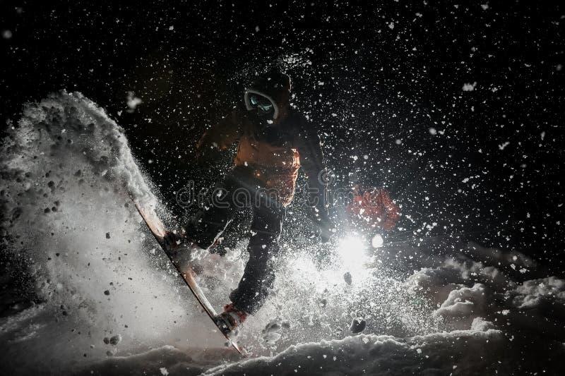Equipaggi lo snowboard strabiliante di guida nello scuro sotto la neve immagine stock libera da diritti