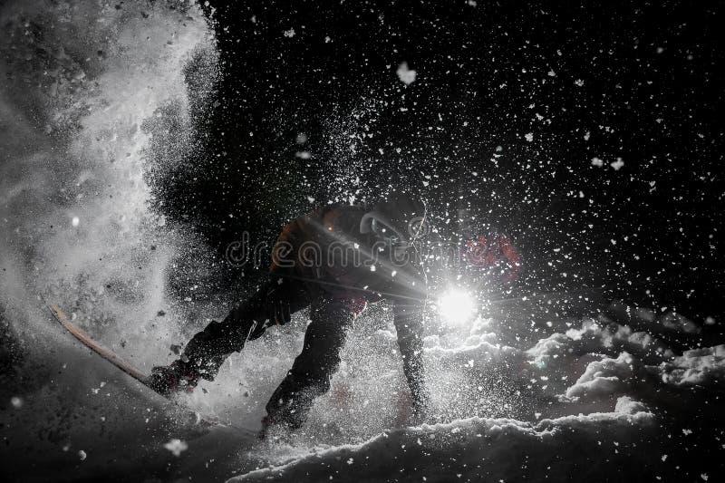 Equipaggi lo snowboard stupefacente di guida nello scuro sotto la neve fotografia stock libera da diritti