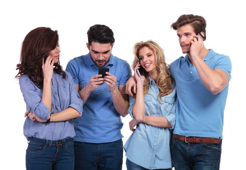 Equipaggi mandare un sms mentre gli amici stanno parlando sul telefono fotografia stock