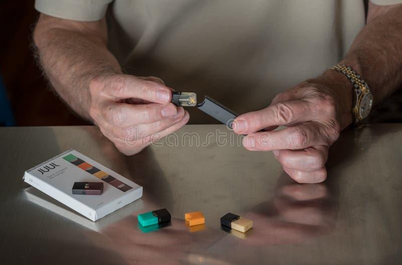 Equipaggi mettere l'erogatore del nicotina di JUUL insieme ai baccelli di sapore fotografia stock libera da diritti