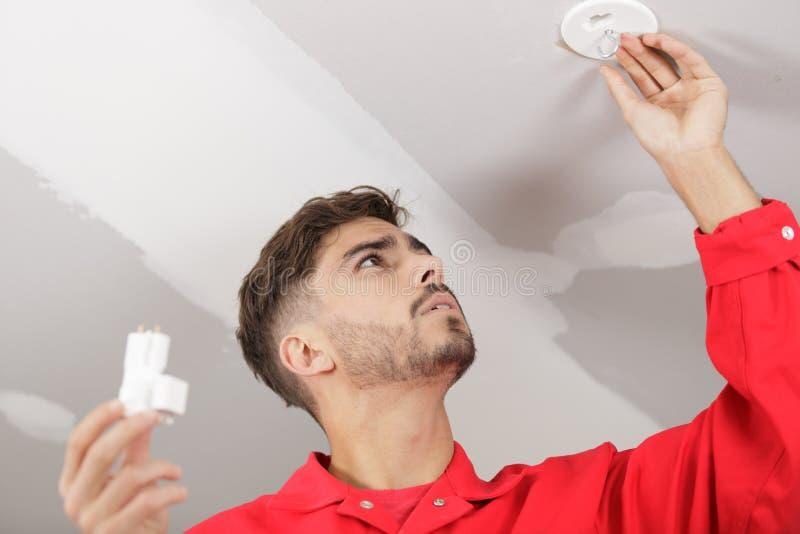 Equipaggi mettere la lampadina di energia bassa LED nella lampada immagini stock