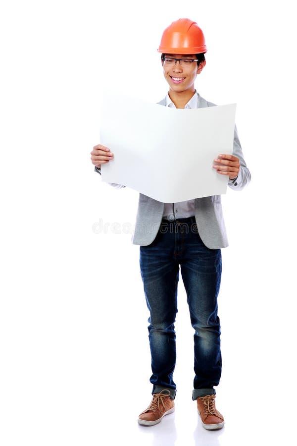 Equipaggi portare un elmetto protettivo che esamina la carta di modello fotografie stock