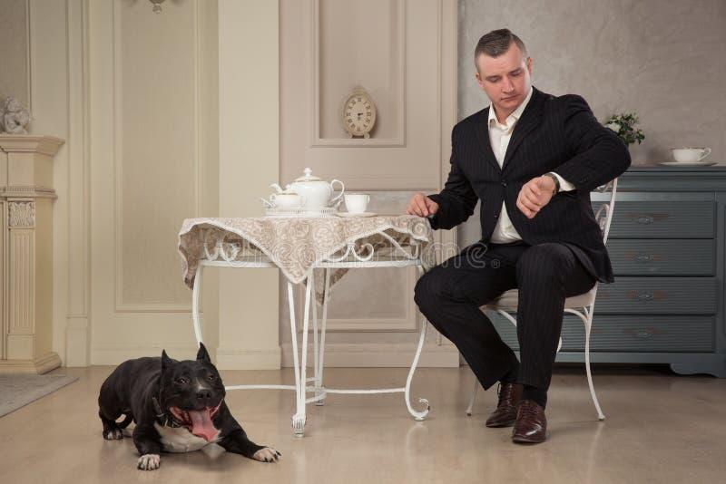 Equipaggi seatting alla tavola e l'esame dell'orologio Vicino alle praterie un pitbull del cane o il nero Staffordshire Terrier n fotografia stock libera da diritti