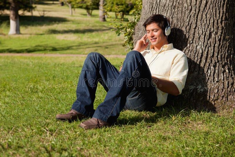 Equipaggi sorridere mentre ascoltano la musica tramite le cuffie mentre con riferimento a fotografia stock libera da diritti