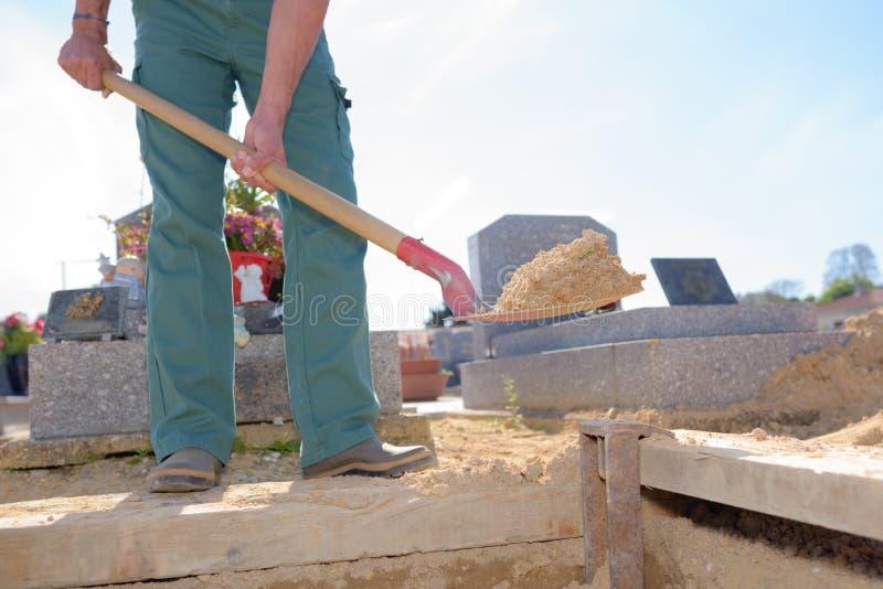Equipaggi spalare la sabbia nella tomba immagine stock libera da diritti