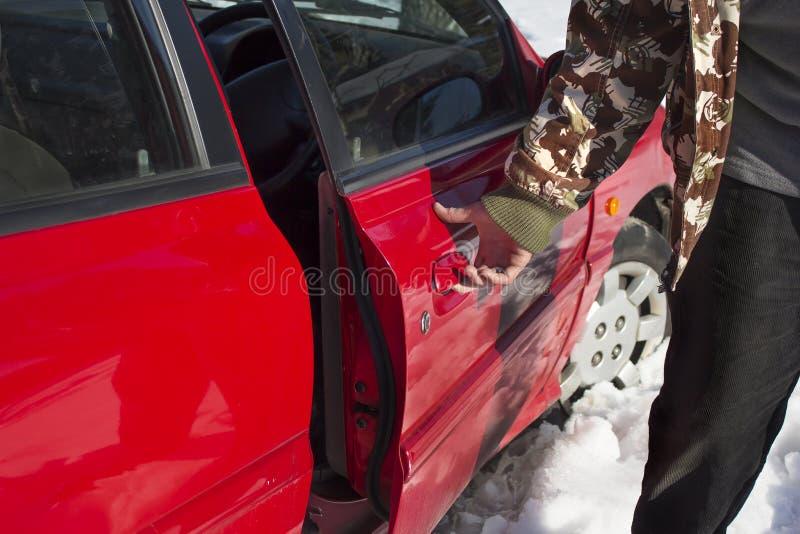 Equipaggi sta tenendo la maniglia ed apre la porta di automobile immagini stock libere da diritti
