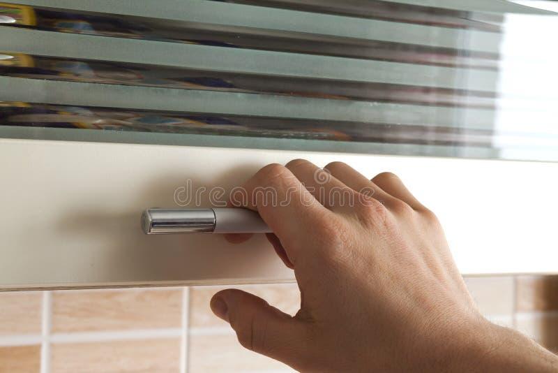 Equipaggia la mano aprono le porte dell'armadietto della cucina, fine  fotografie stock libere da diritti