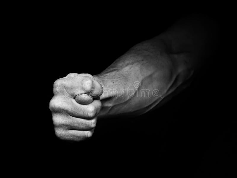 Equipaggia la mano che mostra che il fico firma dentro il buio immagine stock