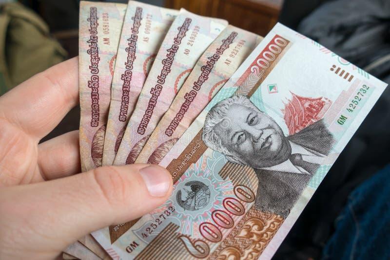 Equipaggia la mano che tiene i fondi del Laos, banconote del kip fotografie stock