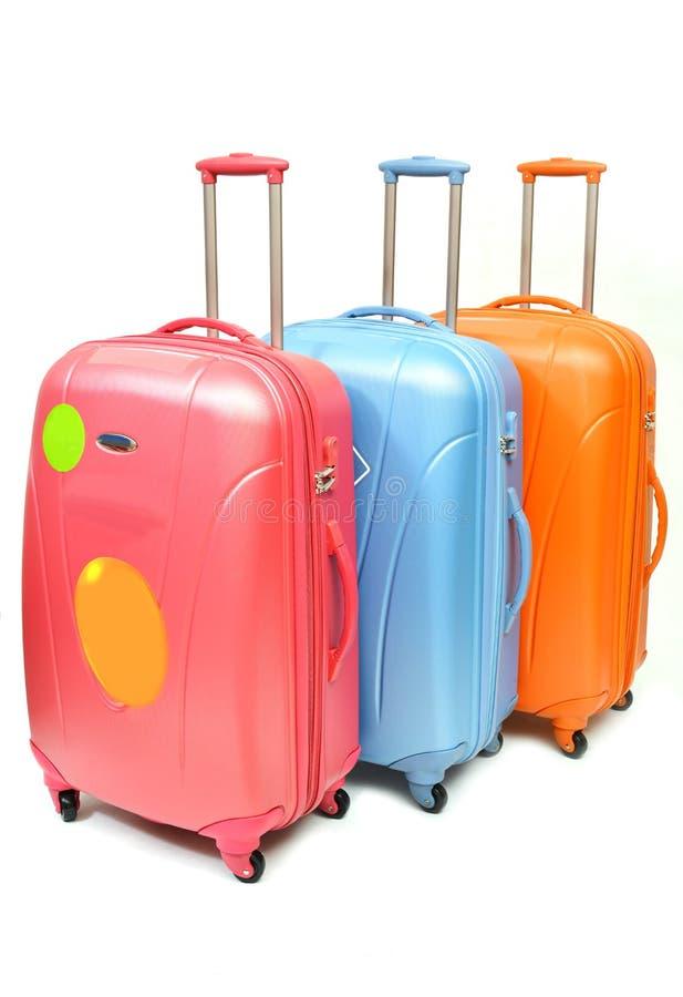 Equipaje anaranjado azul rosado aislado imagen de archivo libre de regalías