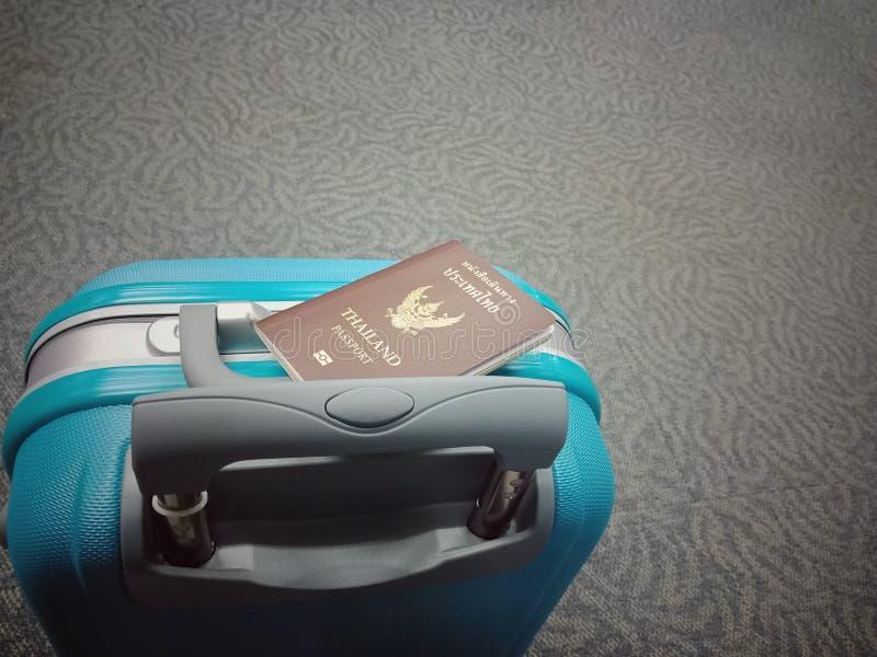 Equipaje azul con un pasaporte en él fotografía de archivo
