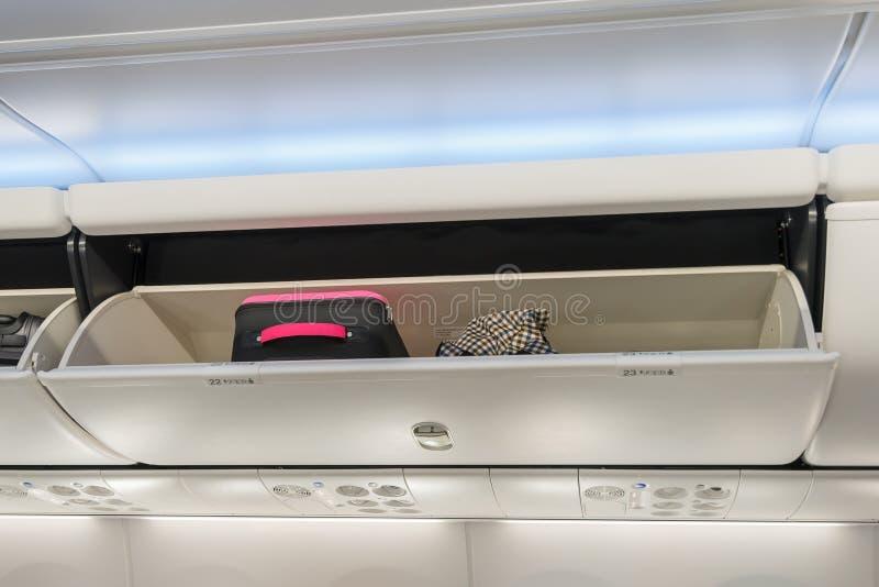 Equipaje de mano en el compartimiento de arriba del almacenamiento en el aeroplano fotos de archivo
