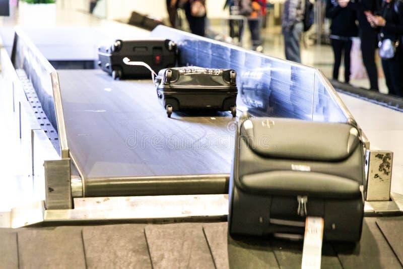 Equipaje del equipaje en la correa del carrusel del transportador en la llegada del aeropuerto fotografía de archivo