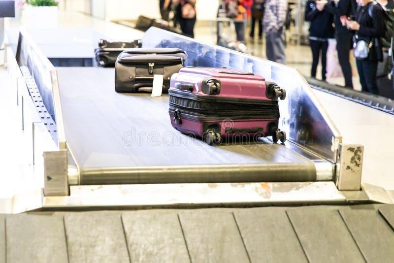 Equipaje del equipaje en la correa del carrusel del transportador en la llegada del aeropuerto fotografía de archivo libre de regalías