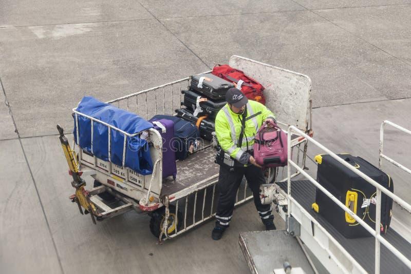 Equipaje que es cargado al aeroplano imagenes de archivo
