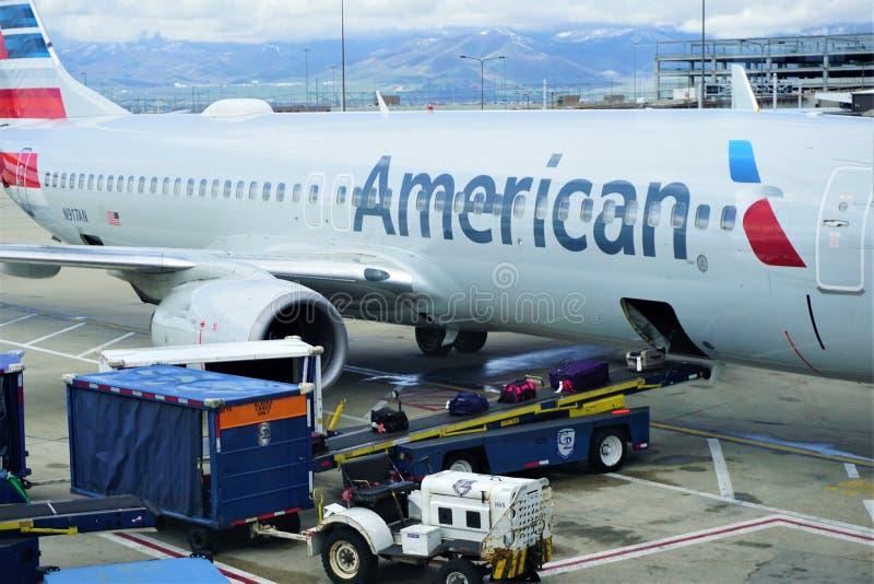Equipaje que es quitado del vuelo de American Airlines imagen de archivo libre de regalías