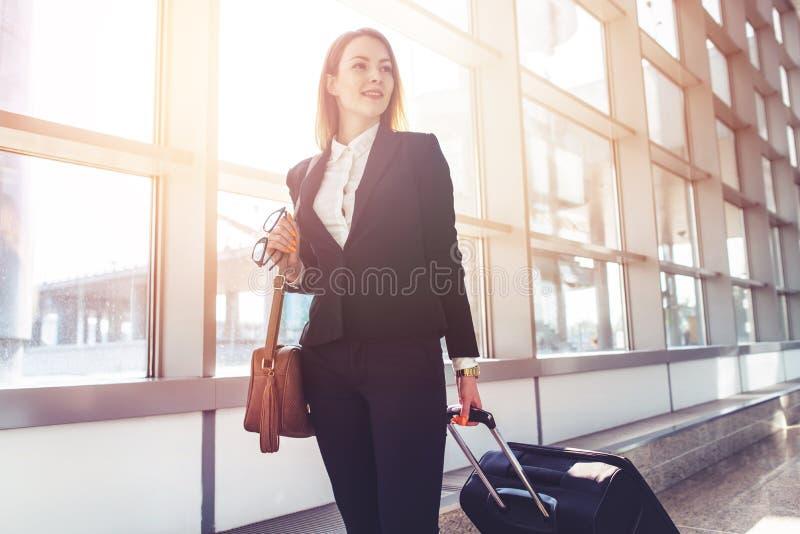 Equipaje que lleva femenino bastante sonriente del asistente de vuelo que va al aeroplano en el aeropuerto imagen de archivo