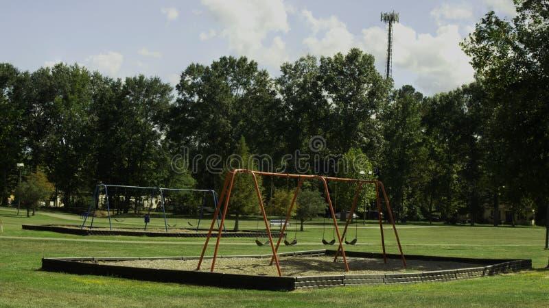 Equipamento colorido do campo de jogos em um parque público com os céus azuis profundos imagem de stock