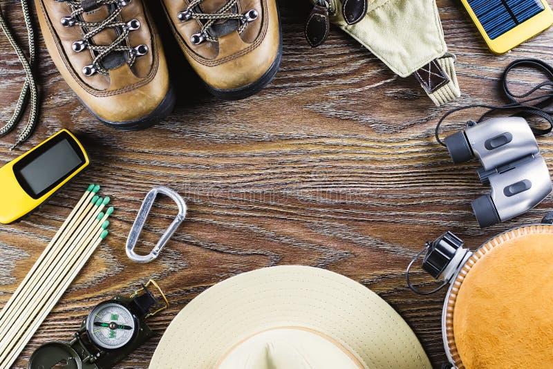 Equipamento com botas, compasso da caminhada ou do curso, binóculos, fósforos no fundo de madeira Conceito ativo do estilo de vid foto de stock