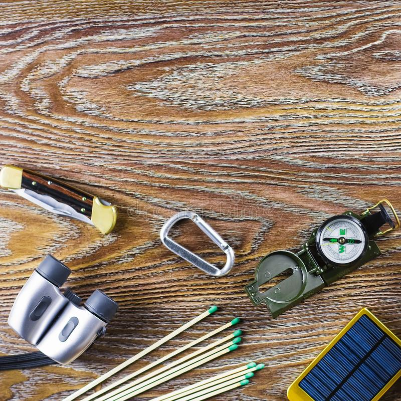 Equipamento da caminhada ou do curso com compasso, binóculos, fósforos no fundo de madeira Conceito ativo do estilo de vida T imagem de stock