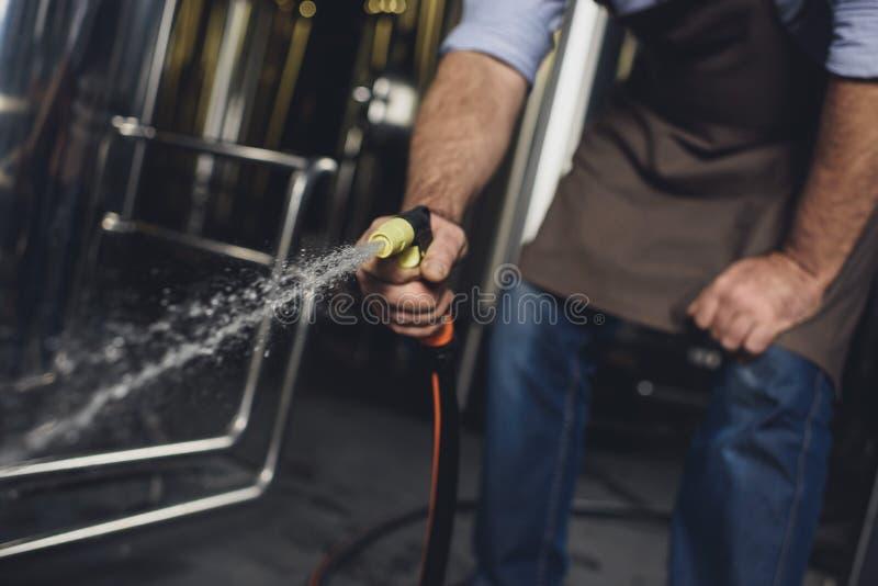 Equipamento da cervejaria da limpeza do trabalhador imagem de stock