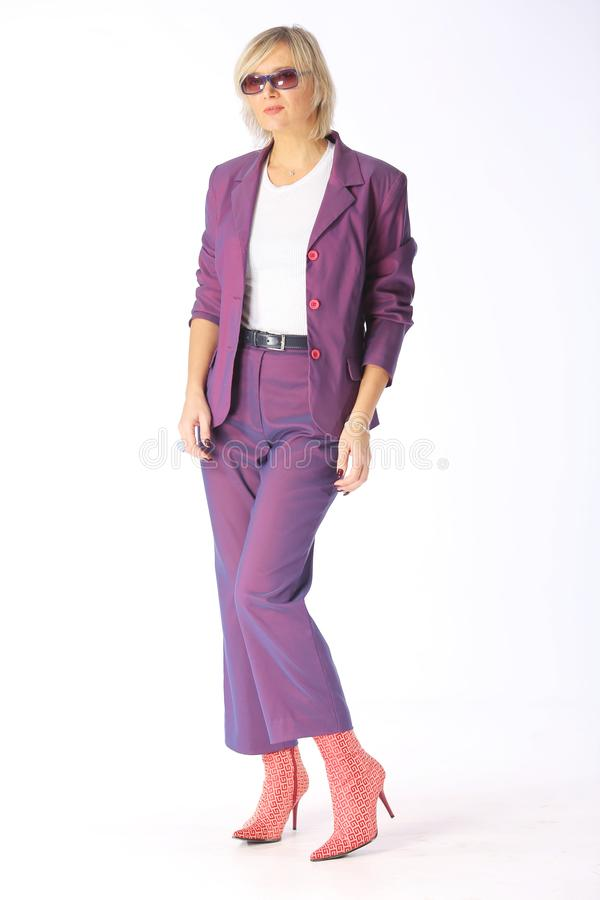 Equipamento da mola, retrato de uma mulher loura nova moderna em um pantsuit lilás roxo e botas com saltos, tiro em um fundo bran foto de stock