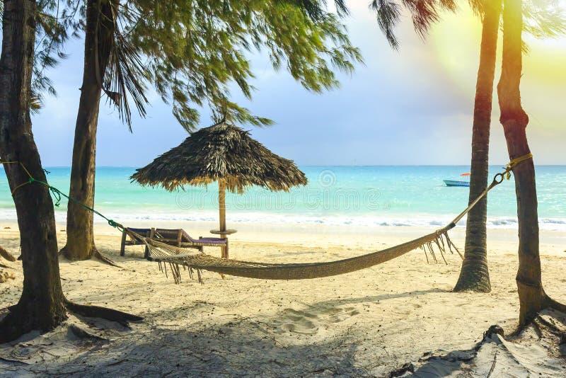 Equipamento da praia da rede, da cadeira e do guarda-chuva feito de materiais naturais em uma praia tropical imagens de stock