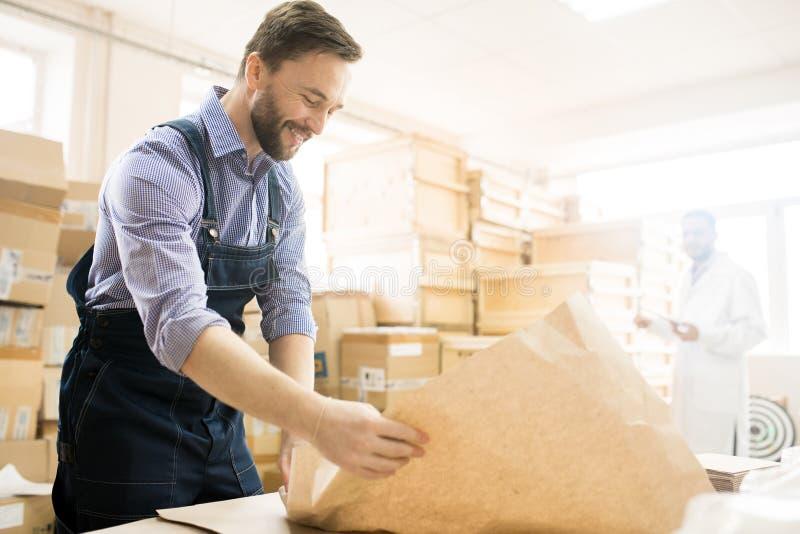 Equipamento de empacotamento de sorriso do trabalhador do armazém imagens de stock