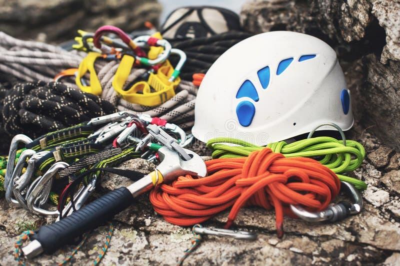 Equipamento de escalada usado - carabiner sem riscos, o martelo de escalada, o capacete branco e corda cinzenta, vermelha, verde  imagens de stock