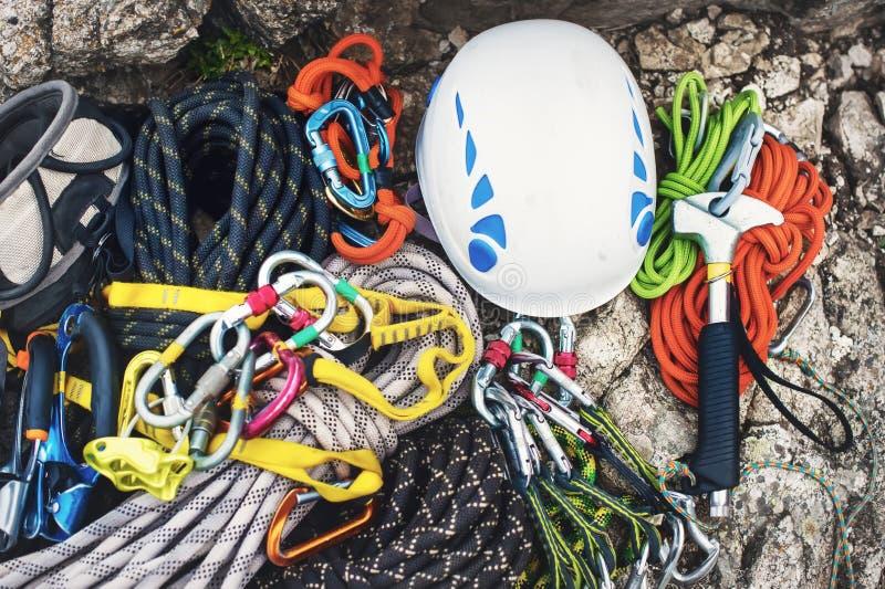 Equipamento de escalada usado - carabiner sem riscos, o martelo de escalada, o capacete branco e corda cinzenta, vermelha, verde  imagem de stock royalty free