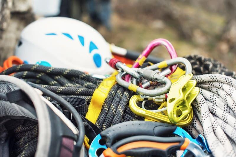 Equipamento de escalada usado - carabiner sem riscos, o martelo de escalada, o capacete branco e corda cinzenta, vermelha, verde  foto de stock