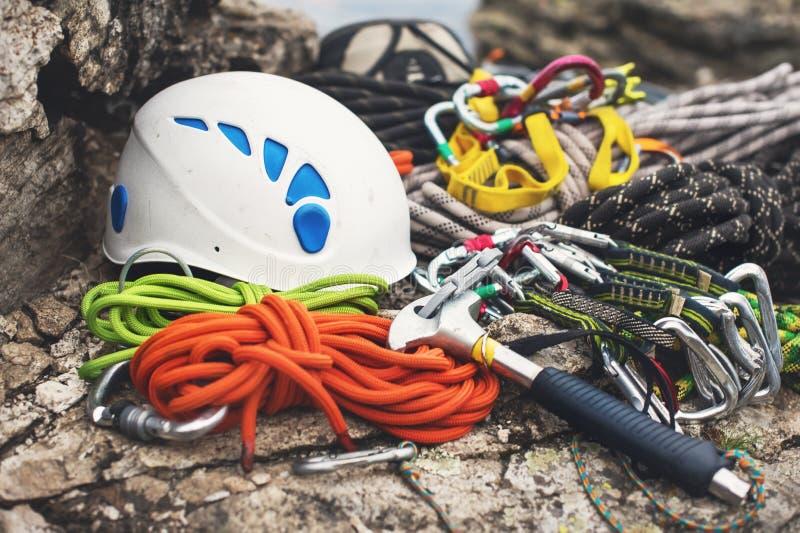 Equipamento de escalada usado - carabiner sem riscos, o martelo de escalada, o capacete branco e corda cinzenta, vermelha, verde  fotografia de stock