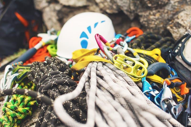 Equipamento de escalada usado - carabiner sem riscos, o martelo de escalada, o capacete branco e corda cinzenta, vermelha, verde  fotos de stock royalty free