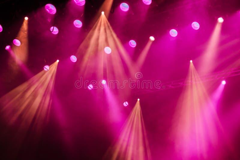 Equipamento de iluminação na fase do teatro durante o desempenho Os raios claros do projetor através do fumo fotografia de stock royalty free