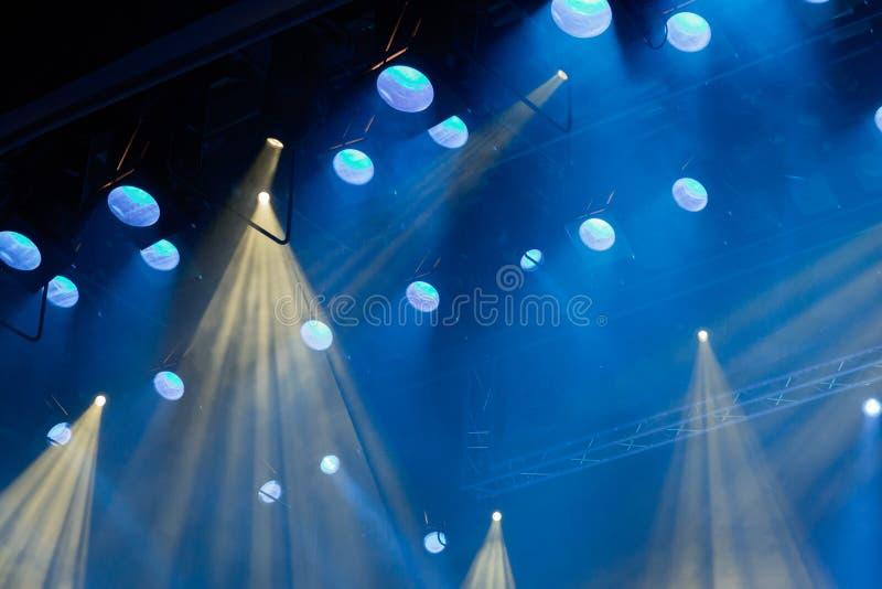 Equipamento de iluminação na fase do teatro durante o desempenho Os raios claros do projetor através do fumo fotos de stock
