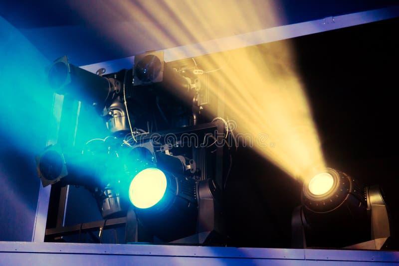 Equipamento de iluminação na fase do teatro durante o desempenho Os raios claros do projetor através do fumo imagem de stock royalty free