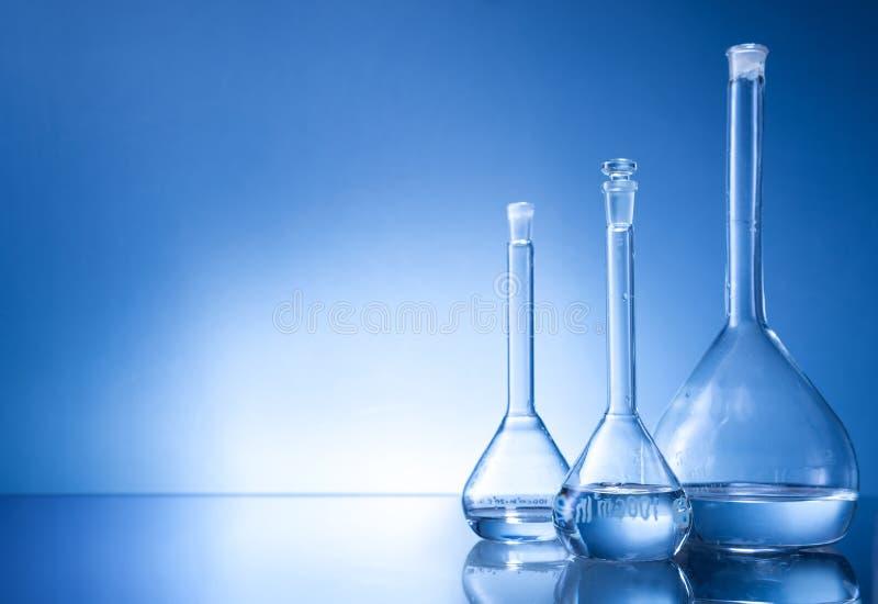 Equipamento de laboratório, garrafa de três vidros no fundo azul imagem de stock