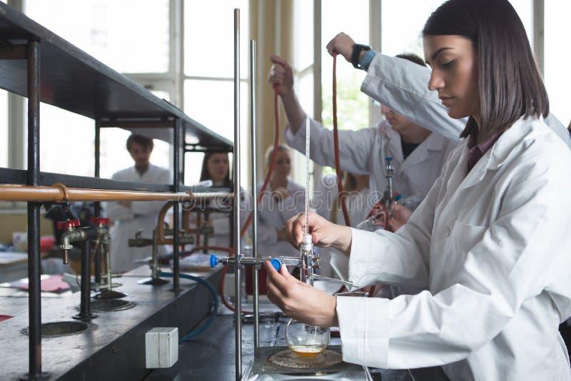 Equipamento de laboratório para a destilação Mãos do estudante/interno/técnico que mostram a experiência Trabalho nas equipes par foto de stock