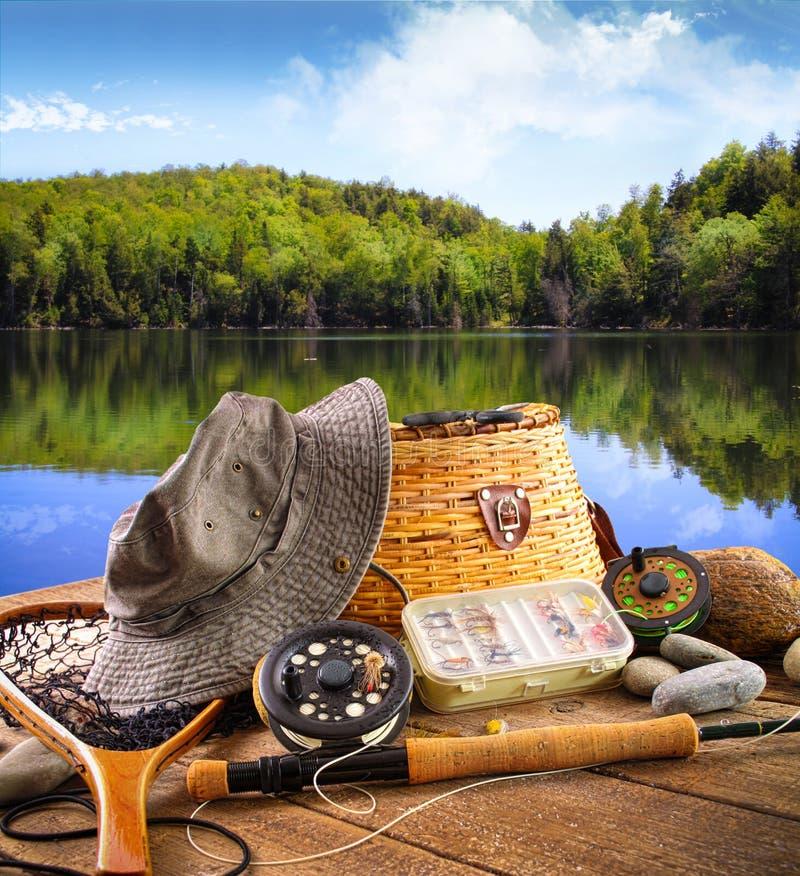 Equipamento de pesca da mosca perto de um lago fotografia de stock royalty free